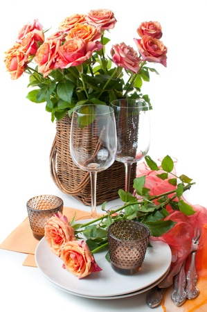 Festive table setting with roses and candles in shades of orange on a white background photo