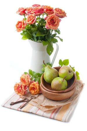 Arrangement with roses and pears in tones orange on a white background photo