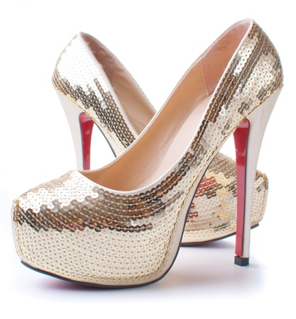 a pair of womens shoes with gold sequins on high heels isolated