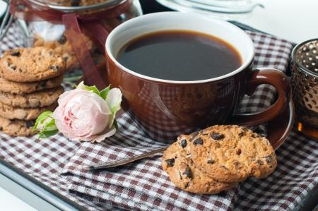 galleta de chocolate: Desayuno fresco, caf� y galletas con chispas de chocolate, en una bandeja con unas servilletas de cuadros