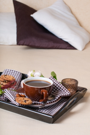 Fresh breakfast, coffee and chocolate chip cookies on a tray on a bed photo