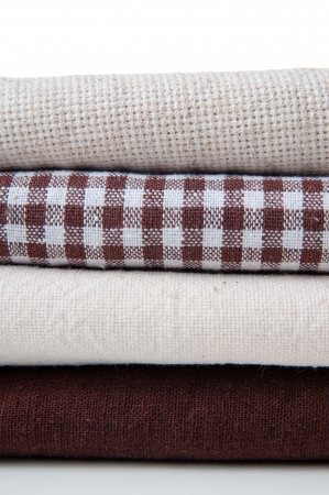 stack of new fabrics in different colors and textures, close-up photo