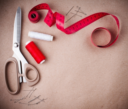 sewing item: Tools for sewing and handmade  thread, scissors, pins on brown paper  Stock Photo