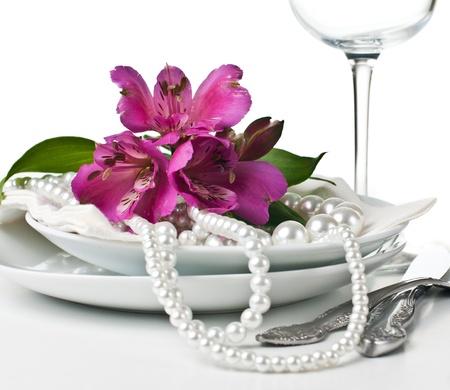 Tabel instelling met roze alstroemeria bloemen, servetten en parels, close-up