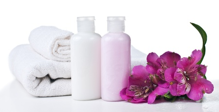 spa still life: resources for spa, white towel, aromatic salt, cream, soap and pink flower, isolated