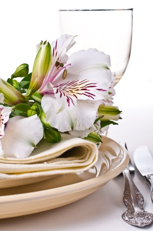 wedding reception: Table setting with white alstroemeria flowers, napkins and yellow plates, close-up