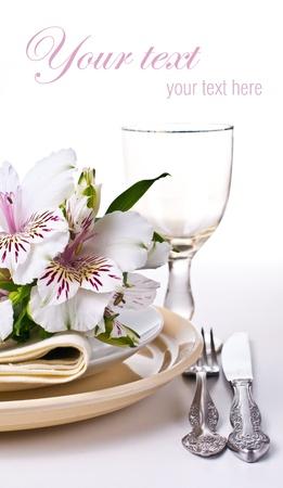 Tabel met witte alstroemeria bloemen, servetten en gele platen, close-up, klaar sjabloon
