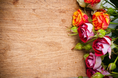 rose coloured: Beautiful bouquet of multicolored roses on a wooden board, close-up, ready background Stock Photo