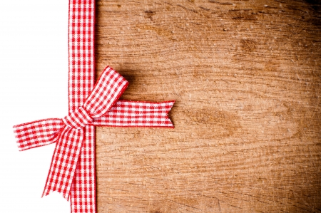 Wooden background with a red checkered ribbon and bow, isolated