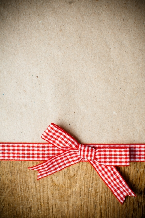 homemade style: Wooden background with a red checkered ribbon and bow on brown kraft paper