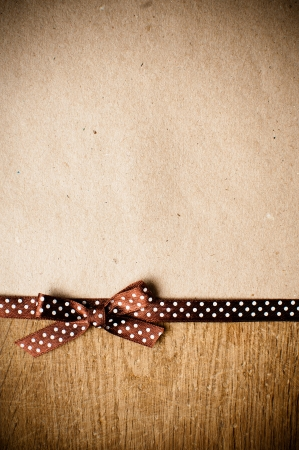 Wooden background with brown polka-dot ribbon and bow on brown kraft paper photo