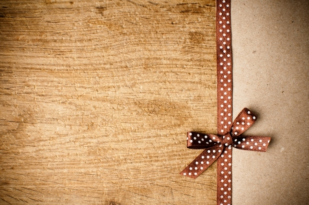 homemade style: Wooden background with brown polka-dot ribbon and bow on brown kraft paper Stock Photo
