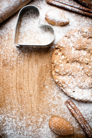 biscuit dough: Christmas and holiday baking background, flour, bakeware, heart, cinnamon, cookies and almonds on a wooden board, viewed from above