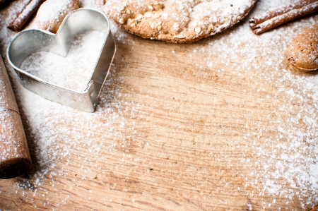 Christmas and holiday baking background, flour, bakeware, heart, cinnamon, cookies and almonds on a wooden board, viewed from above photo