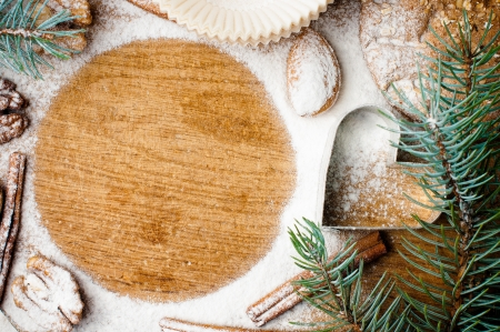 Christmas and holiday baking, cookies, flour, spruce branches and round space for text on a wooden board, ready template photo