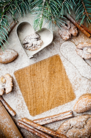 Christmas and holiday baking, cookies, flour, spruce branches and square space for text on a wooden board, ready template photo