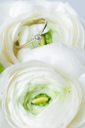 Golden engagement ring with diamond in a white flower close-up photo