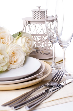 candle light dinner: Festive table setting with beige roses, wine glasses, candles, napkins and cutlery Stock Photo