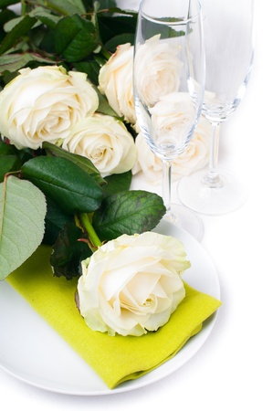 china rose: Festive table setting with beige roses, wine glasses, candles, napkins and cutlery, isolated Stock Photo