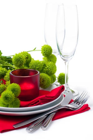 candle light dinner: Festive table setting with chrysanthemums, glasses, candles, napkins and cutlery in red and green colors Stock Photo