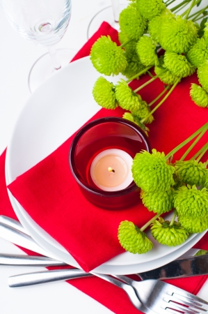 Festive table setting with chrysanthemums, glasses, candles, napkins and cutlery in red and green colors Stock Photo