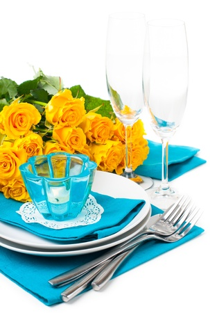 china rose: Festive table setting with yellow roses, glasses, candles, napkins and cutlery in blue and yellow colors