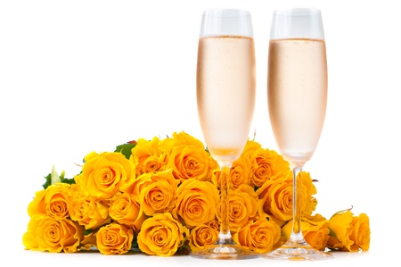 Two glasses of cold champagne and a large bouquet of yellow roses on a white background, isolated photo