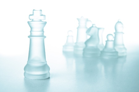 alone in crowd: Success and leadership concept, glass chess piece king on a white background isolated.