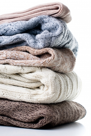 multi layered: A stack of warm winter knitted sweaters on a white background isolated.