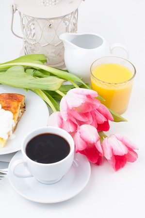 Elegantly served breakfast, a cup of coffee, flowers, and orange juice on white background, isolated photo