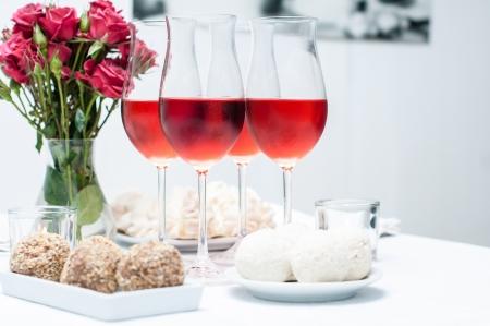 Rose wijn in glazen, verse bloemen, gebak en snacks op de feesttafel, home party