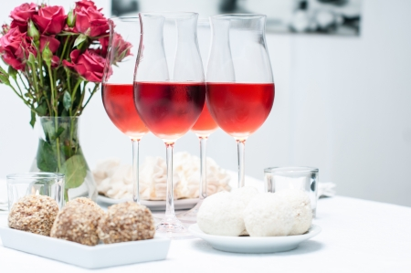 Rose wine in glasses, fresh flowers, cakes, and snacks on the festive table, home party