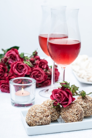 winetasting: Two glasses of rose wine , fresh flowers, cakes, and snacks on the festive table, home party Stock Photo