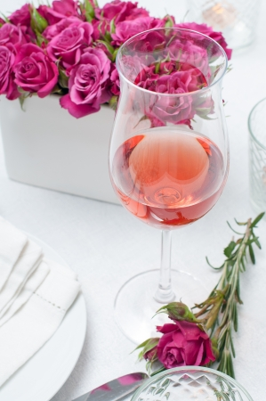 rose wine: A glass of rose wine and festive dining table setting with pink roses, white tablecloths and napkins, candles, holiday dinner