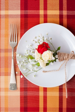 Festive table setting with flowers and vintage crockery on the bright checkered tablecloth in a country style photo