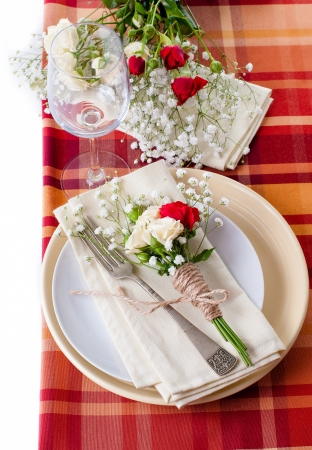 checker plate: Festive table setting with flowers and vintage crockery on the bright checkered tablecloth in a country style