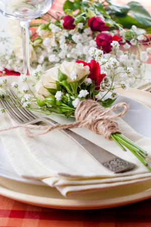 wedding table setting: Festive table setting with flowers and vintage crockery on the bright checkered tablecloth in a country style, closeup