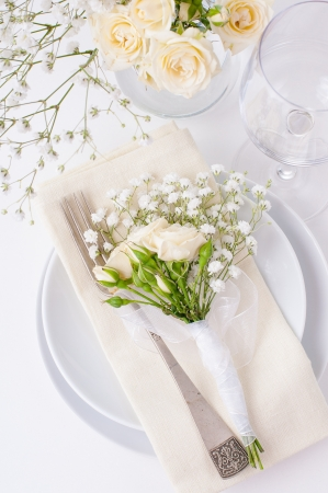 Festive table setting with roses in bright colors and vintage crockery on a white background photo