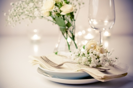 flower arrangement white table: Festive table setting with roses in bright colors and vintage crockery on a beige background