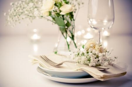 Festlich gedeckten Tisch mit Rosen in leuchtenden Farben und Vintage-Geschirr auf einem beige Hintergrund Standard-Bild