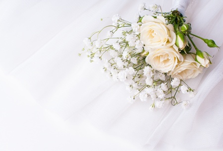 tulle: small bouquet of white roses and gypsophilas on a white tulle