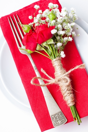 Festive table setting with red roses, napkins and vintage crockery on a white background photo