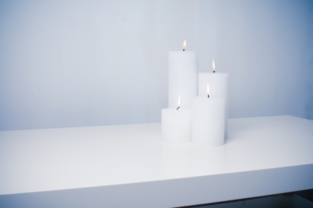 candle flame: four white candles burning on a white table in an interior