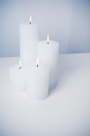 four white candles burning on a white table in an interior photo