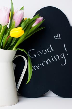 buen vivir: ramo de tulipanes en una jarra blanca y pizarra con la inscripción sobre un fondo blanco