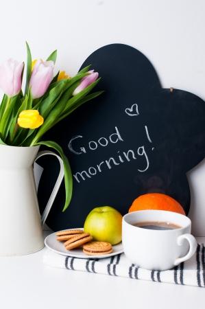 boeket van tulpen in een witte kruik, 's ochtends koffie, fruit en krijt bord met het opschrift op een witte achtergrond Stockfoto