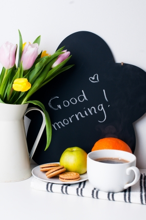 bouquet of tulips in a white jug, morning coffee, fruit and chalk board with the inscription on a white background photo