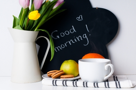 good morning: bouquet of tulips in a white jug, morning coffee, fruit and chalk board with the inscription on a white background