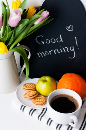 morning coffee: bouquet of tulips in a white jug, morning coffee, fruit and chalk board with the inscription on a white background