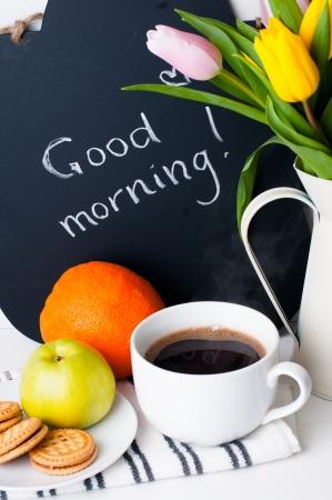 아침: 흰색 배경에 비문 흰색 조끼, 모닝 커피, 과일과 분필 보드에 튤립의 꽃다발 스톡 사진
